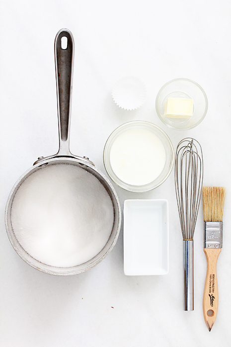 Picture of all the things needed for the recipe including pot filled with sugar, dishes of water, sugar, butter, as well as a whisk and pastry brush.