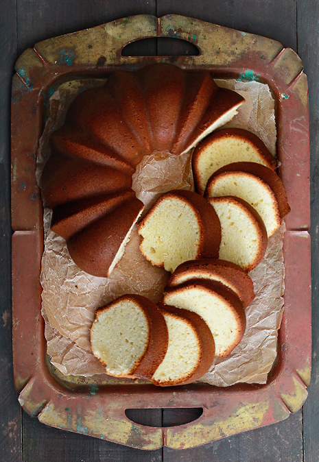 Pound cake partially sliced up into pieces arranged on a platter.