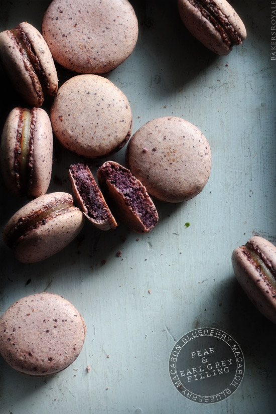 Ten Blueberry Macarons with Pear & Earl Grey Filling on counter.