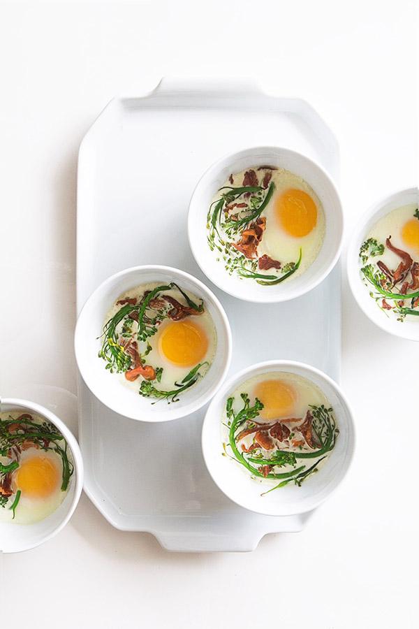 Five ramekins filled with eggs en cocotte.