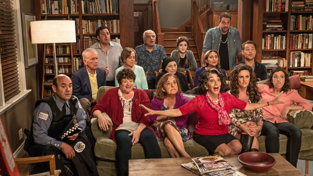 The cast of My Big Fat Greek Wedding 2 sitting on and behind a couch watching television.