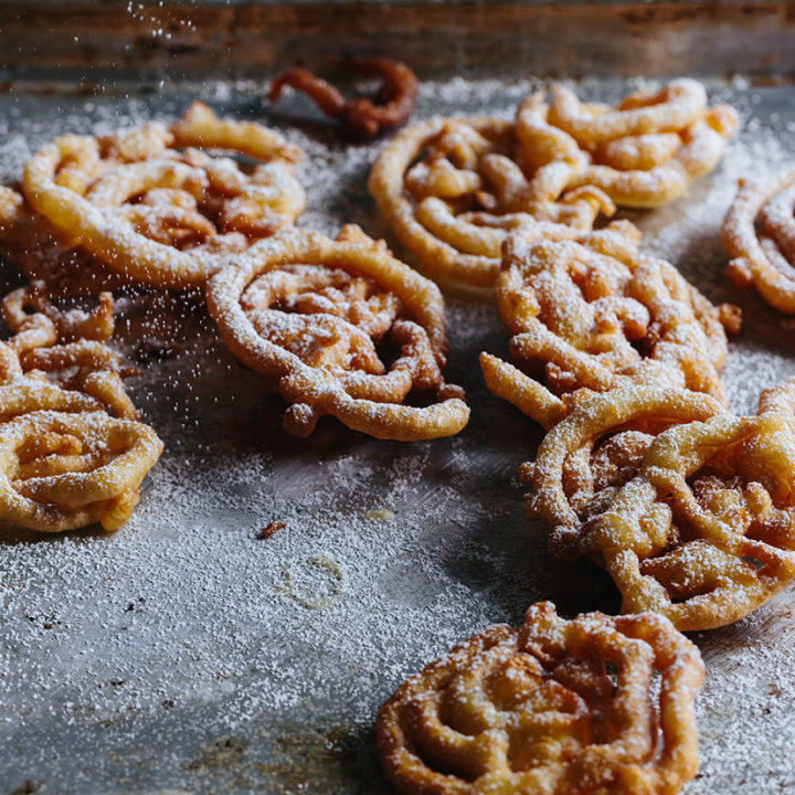 a counter full of small funnel cakes sprinkled with powdered sugar.