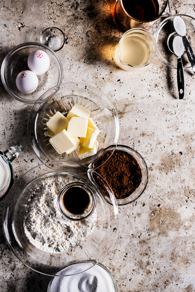Ingredients to make chocolate rum cake including dishes of eggs, butter, cocoa, flour, sugar, and vanilla. There are spoons full of baking soda and cups full of rum and ginger beer.