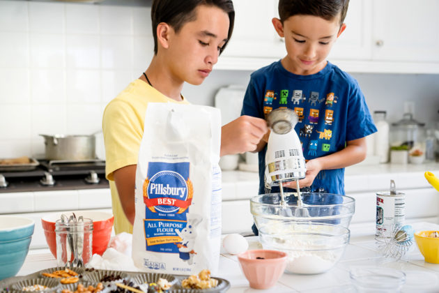 The kids adding flour and using a hand mixer to make batter.